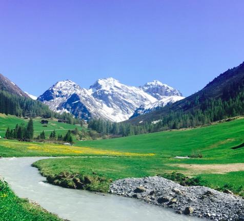 schneebedeckte Berge in der Schweiz, weites Tal mit grünen Wiesen